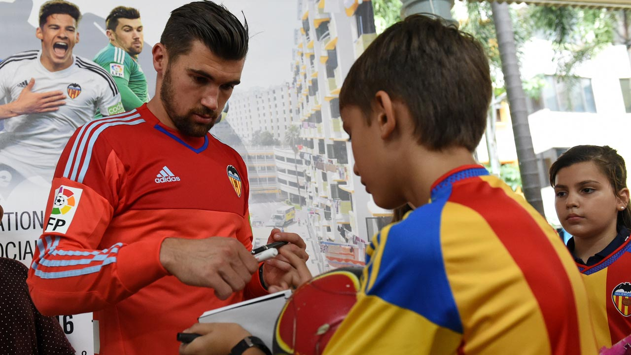 Valencia's CF Spanish footballer Mathew Ryan (L) signs authographs during a neighbourhood youth community event at Bukit Ho Swee in Singapore on May 18, 2016. AFP