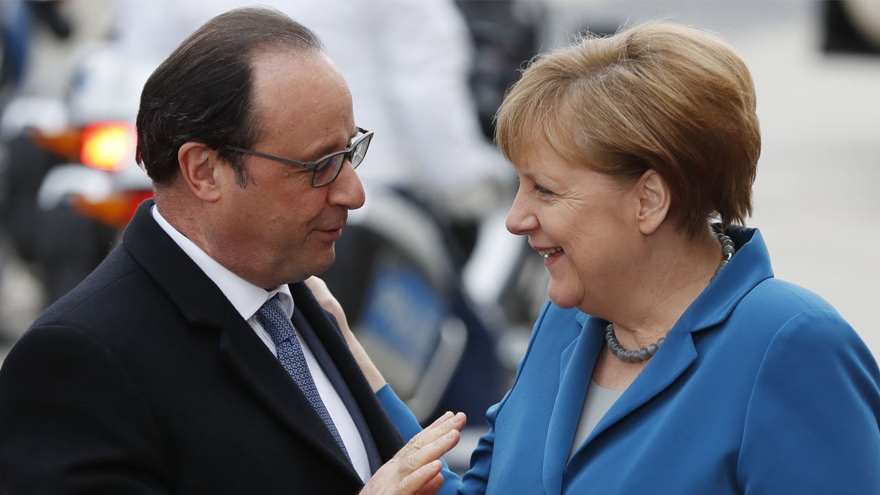 German Chancellor Angela Merkel (R) welcomes French President Francois Hollande as he arrives for an informal meeting at the Herrenhausen Palace in Hanover, on April 25, 2016. German Chancellor Angela Merkel meets Britain's Prime Minister David Cameron, French President Francois Hollande, Italian Prime Minister Matteo Renzi and US President Barack Obama for informal talks at the Herrenhausen Palace. / AFP PHOTO / ODD ANDERSEN