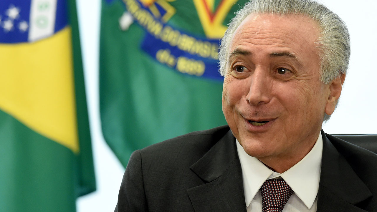 Brazilian acting President Michel Temer gestures during a meeting with unions' representatives at Planalto Palace in Brasilia, May 16, 2016. Street protests and controversy over the absence of female ministers clouded Brazilian acting President Michel Temer's political honeymoon Monday as he began his first full week in power. / AFP PHOTO / EVARISTO SA