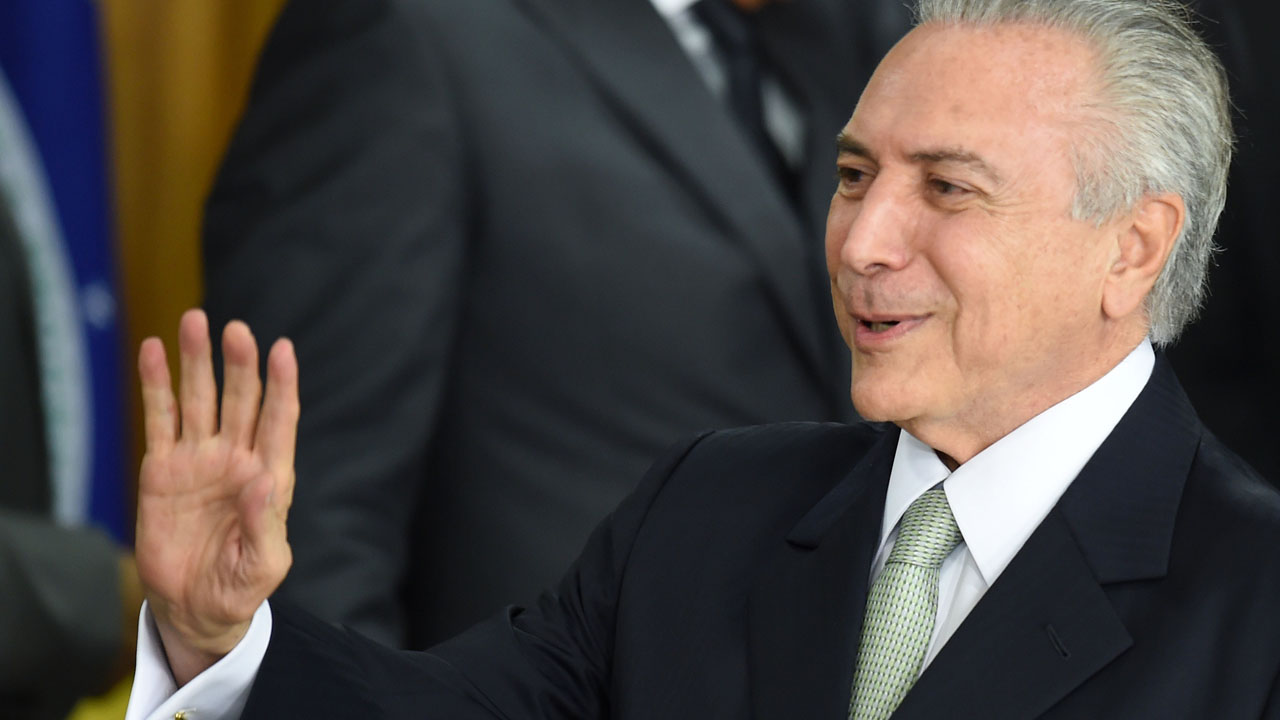 Brazilian acting President Michel Temer gestures during the inauguration ceremony of the new ministers at Planalto Palace, in Brasilia, on May 12, 2016. Brazilian President Dilma Rousseff was suspended Thursday to face an impeachment trial, ceding power to her vice president-turned-enemy Michel Temer, who quickly pivoted toward a more business-friendly government, naming a cabinet chosen to calm the markets after a paralyzing impeachment battle and steer the country out of its worst recession in decades.  / AFP PHOTO / EVARISTO SA /