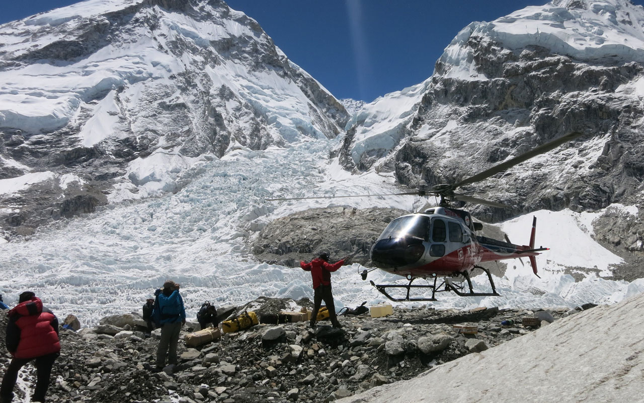 This handout photograph released by Phurba Tenzing Sherpa on May 24, 2016, shows mountaineers gathering as a helicopter lands at Everest Base Camp on May 15, 2016.  Rescuers searching for two Indian climbers missing on Mount Everest said that there was little hope of finding the pair alive after losing contact with them over the weekend. / AFP PHOTO / PHURBA TENZING SHERPA / HO /