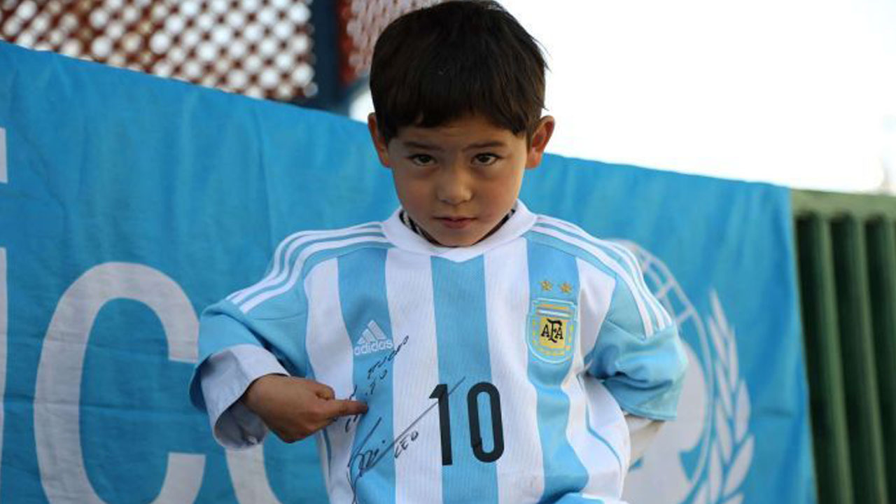 Photo: Murtaza Ahmadi posing with a jersey sent to him by Argentine football star Lionel Messi. (AFP/UNICEF)