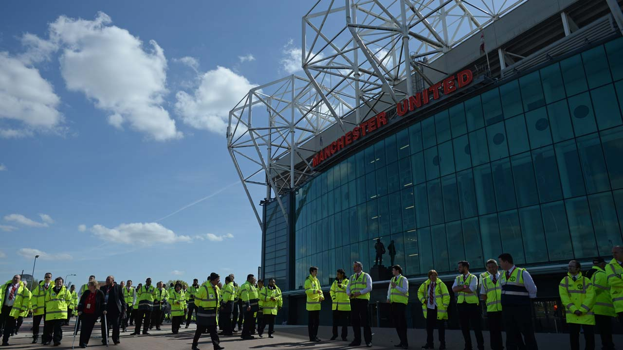Evacuated stewards wait outside Old Trafford stadium in Manchester, north west England, on May 15, 2016, after the English Premier League football match between Manchester United and Bournemouth was abandoned. Police ordered Manchester United to abandon their final Premier League game of the season against Bournemouth on Sunday after a suspicious package was discovered at Old Trafford. OLI SCARFF / AFP