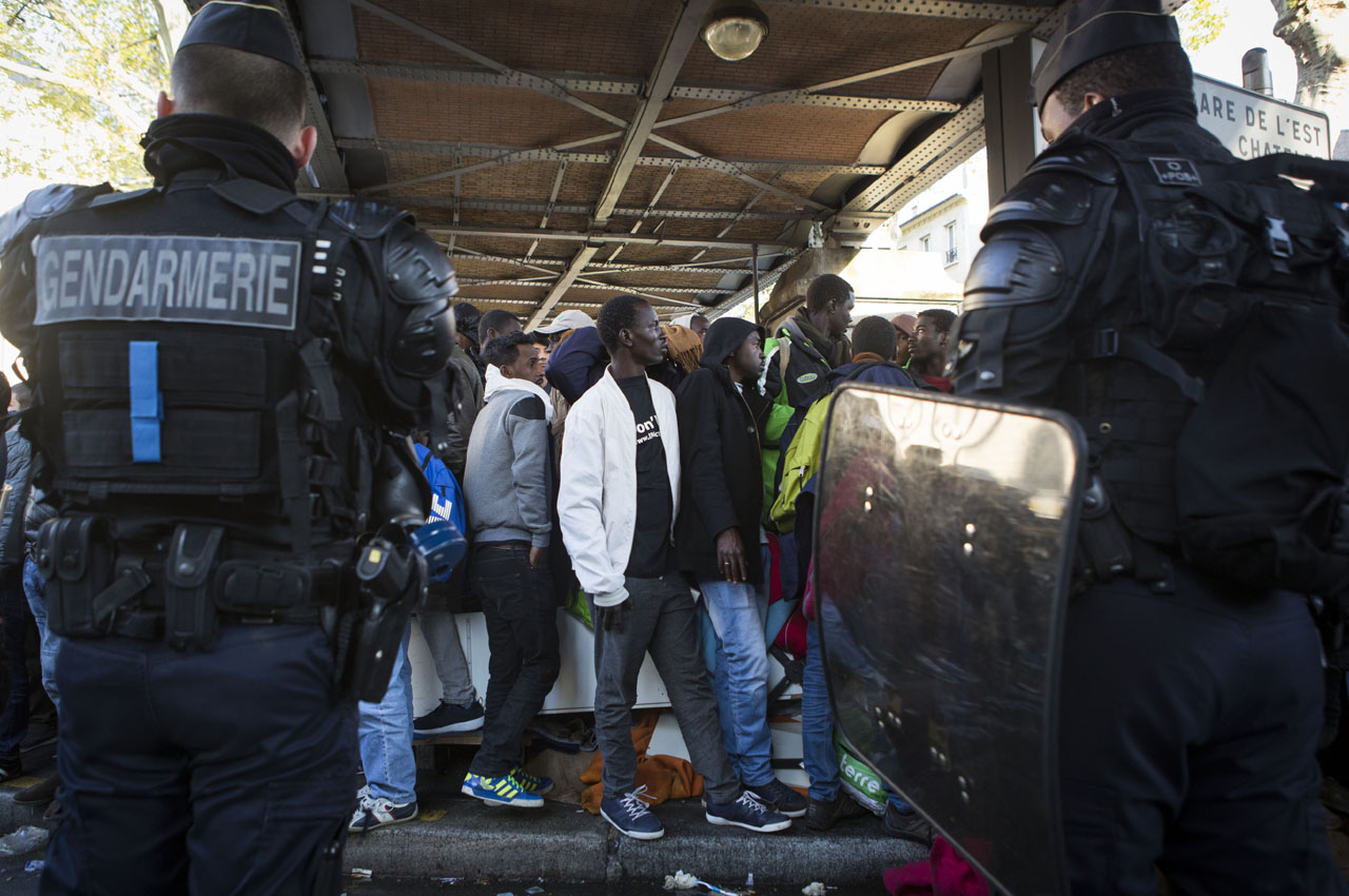 Migrants are evacuated by French police officers and gendarmes  from a makeshift camp under the Stalingrad metro station in Paris, on May 2, 2016. / AFP PHOTO / Geoffroy Van der Hasselt