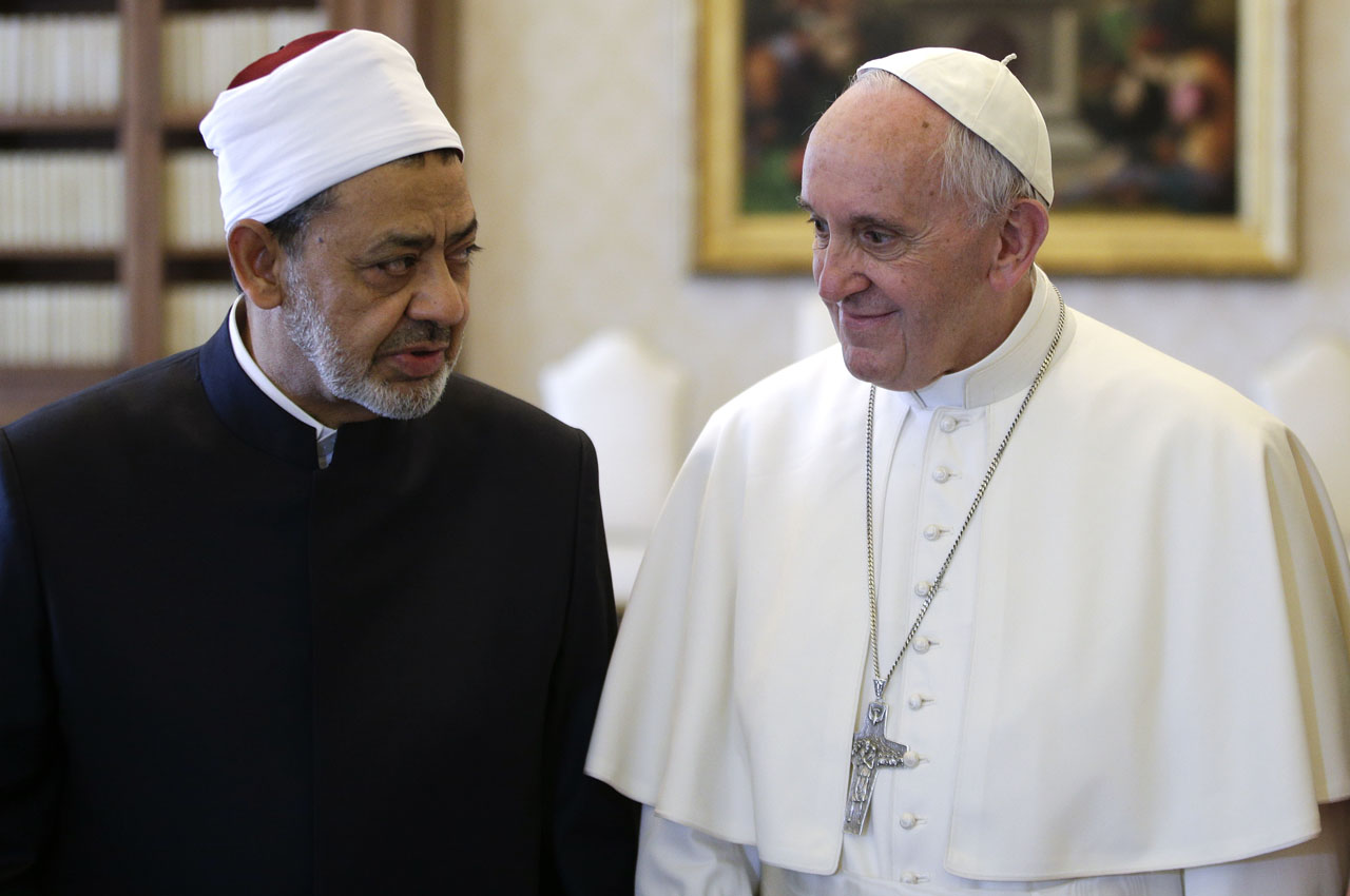 Pope Francis (R) talks with Egyptian Imam of al-Azhar Mosque Sheikh Ahmed Mohamed el-Tayeb (L) during a private audience at the Vatican on May 23, 2016.  Pope Francis met the grand imam of Cairo's Al-Azhar Mosque at the Vatican on Monday in a historic encounter that was sealed with a hugely symbolic hug and exchange of kisses. / AFP PHOTO / POOL / MAX ROSSI
