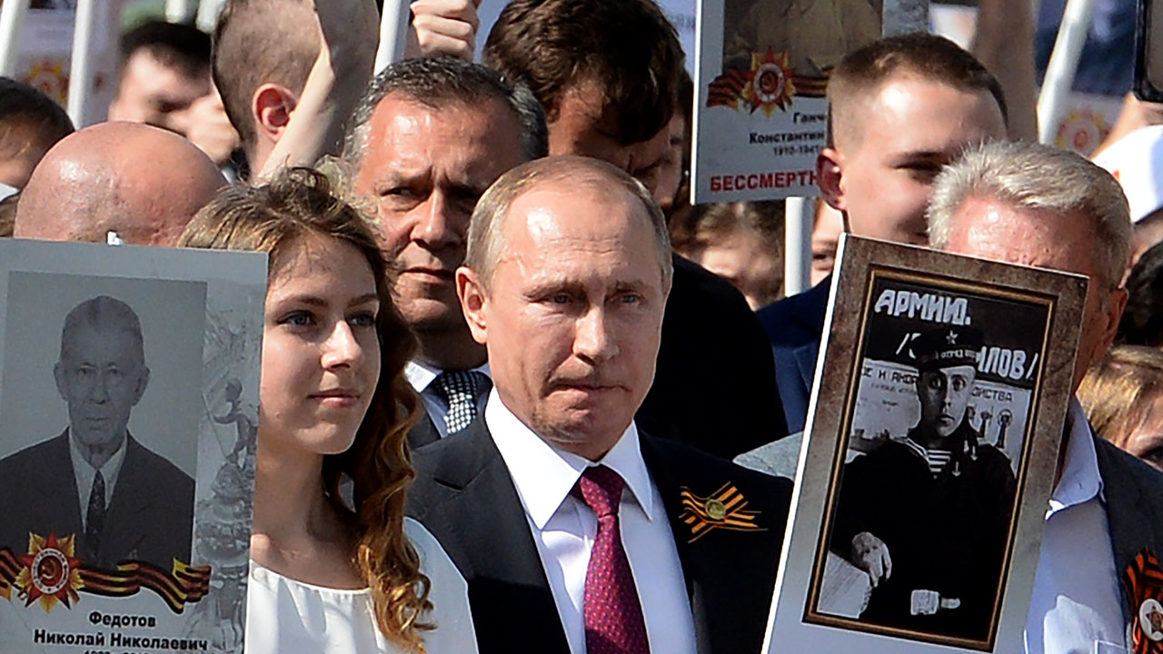 Russian President Vladimir Putin (C) carries a portrait of his father Vladimir as he takes part in the Immortal Regiment march in Moscow on May 9, 2016.  Russia marks the 71st anniversary of the Soviet Union's victory over Nazi Germany in World War II. / AFP PHOTO / VASILY MAXIMOV