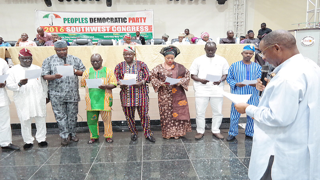 Former Governor of Rivers State, Celestine Omehia (right), administering oath of office to the newly elected Southwest PDP executives at Akure, Ondo State.