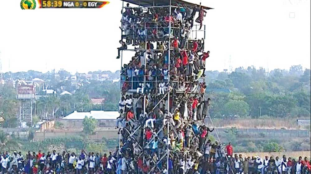 Spectators climbed electronic scoreboard and other platforms to watch the Gabon 2017 AFCON qualifier between the Super Eagles clash and Egypt in March. CAF fined Nigeria for poor crowd control during the game…recently.