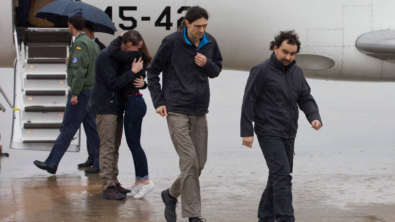 handout photo released by Presidencia del Gobierno and taken on May 8, 2016 shows Spanish freelance journalists Angel Sastre (R), Jose Manuel Lopez (C) and Antonio Pampliega (2nd L) arriving at Torrejon military airport in Madrid. The three Spanish freelance journalists who were kidnapped in Syria nearly 10 months ago returned to Spain on May 8, 2016 to be reunited with their families.  HO Diego Crespo / Presidencia del Gobierno / AFP
