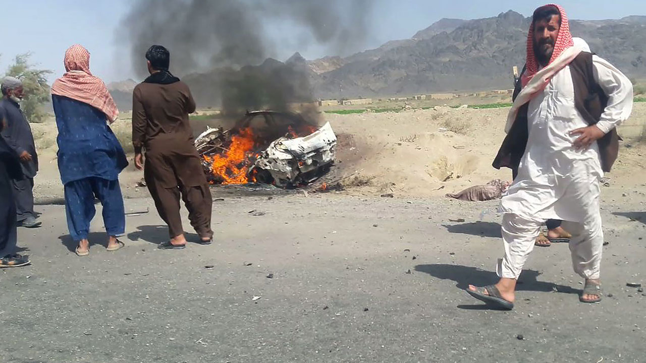 This photograph taken on May 21, 2016 shows Pakistani local residents gathering around a destroyed vehicle hit by a drone strike in which Afghan Taliban Chief Mullah Akhtar Mansour was believed to be travelling in the remote town of Ahmad Wal in Balochistan, around 160 kilometres west of Quetta. Afghan authorities scrambled May 22 to confirm the fate of Taliban leader Mullah Akhtar Mansour after US officials said he was likely killed in drone strikes -- a potential blow to the resurgent militant movement.  / AFP PHOTO / -