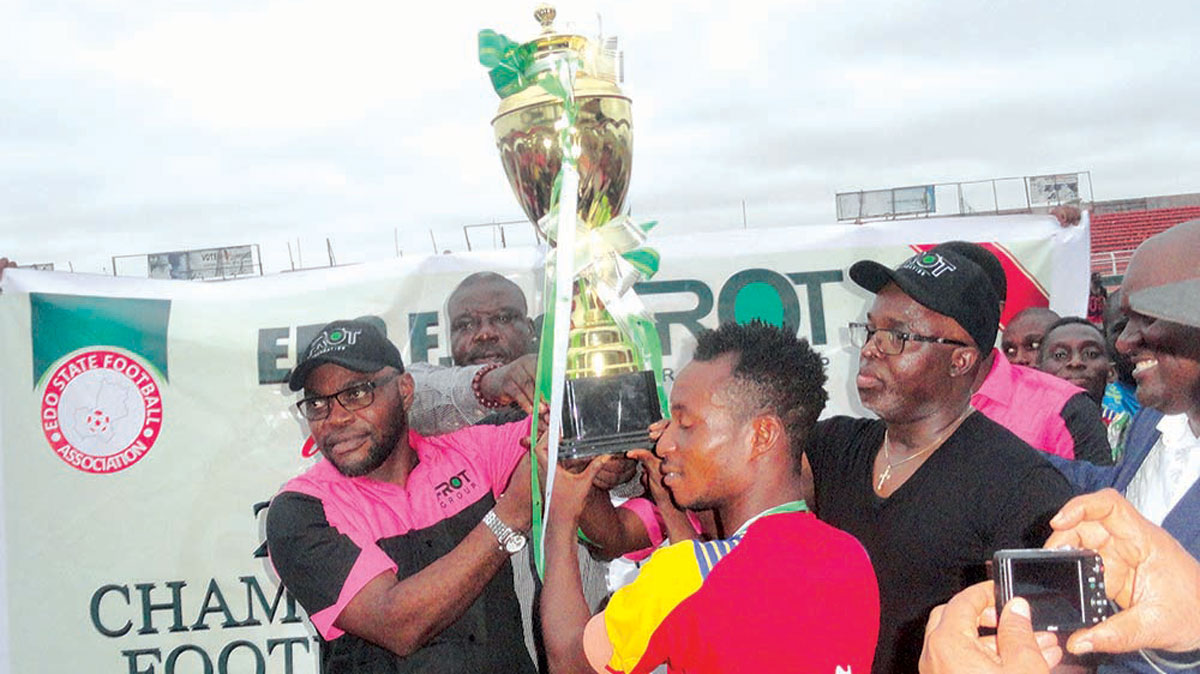 FROT Group President, Frank Momoh (left), and NFF President, Amaju Pinnick (left), presenting the South South Champion of Champions trophy to Bendel Insurance Captain, William U., at the end of the competition…on Saturday.