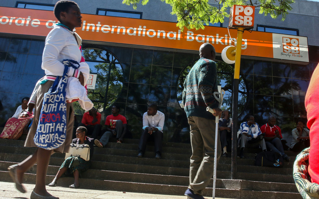 """Zimbabweans queue to withdraw cash outside a bank on May 5, 2016 in Harare, Zimbabwe.   Zimbabweans formed long queues outside banks Thursday after the government slapped new limits on cash withdrawals and announced that """"bond notes"""" at par with the US dollar would be introduced. / AFP PHOTO / JEKESAI NJIKIZANA"""