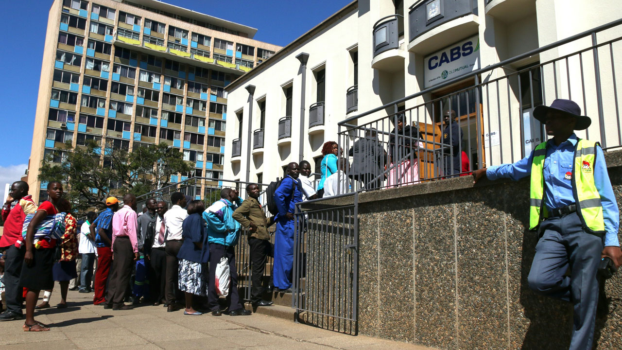 """Zimbabweans queue to withdraw cash outside a bank on May 5, 2016 in Harare, Zimbabwe.   Zimbabweans formed long queues outside banks on May 5 after the government slapped new limits on cash withdrawals and announced that """"bond notes"""" at par with the US dollar would be introduced. / AFP PHOTO / JEKESAI NJIKIZANA"""
