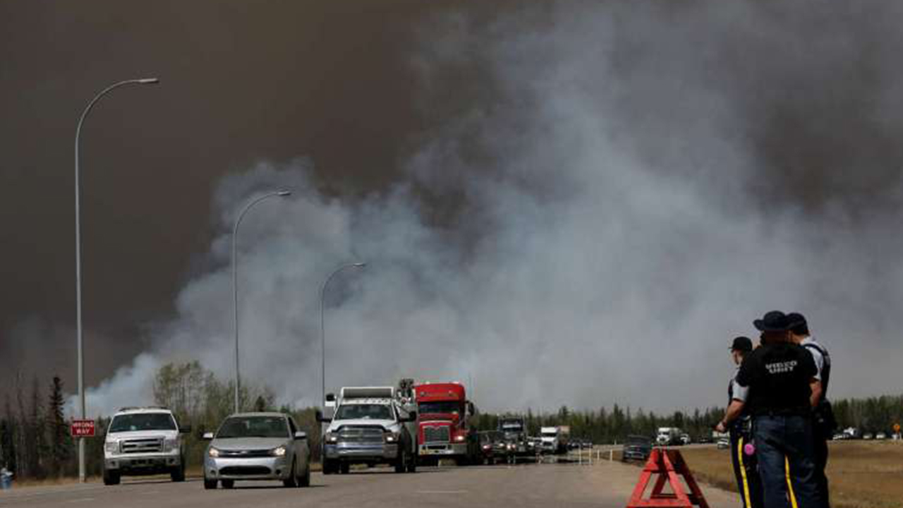 Canadian police led convoys of cars through the burning ghost town of Fort McMurray on Friday in a risky operation to get thousands of people to safety on the other side.