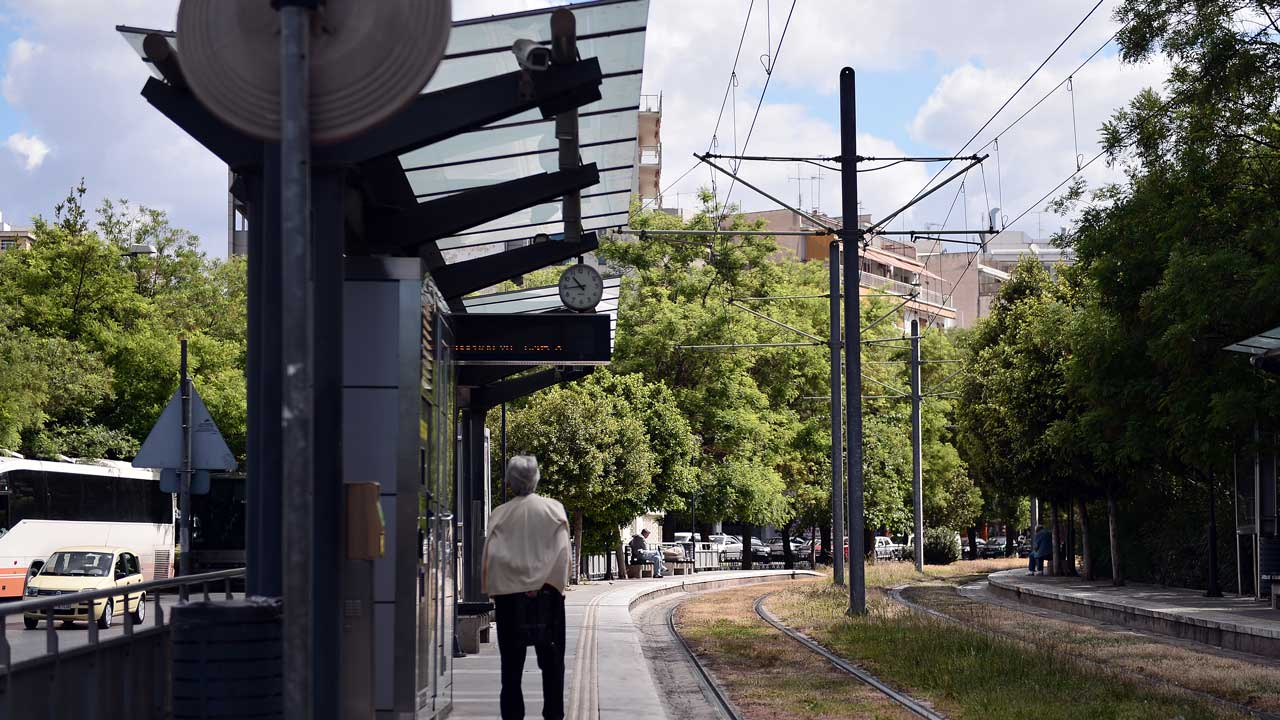 A woman reads an announcement informing about 48-hours strike as she stands at a closed tram station in Athens, on May 6, 2016. Greece's labour unions stage a two-day general strike to protest against controversial government plans to overhaul pensions and increase taxes to meet demands of its bailout creditors. LOUISA GOULIAMAKI / AFP