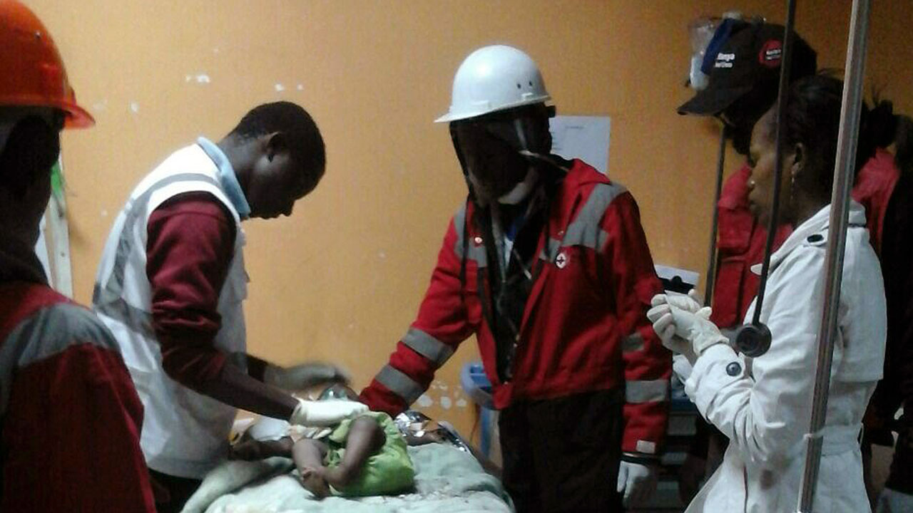 "A handout picture taken and released on May 3, 2016 by Kenya Red Cross shows Kenyan Red Cross staff with a 18-month-old toddler rescued alive from the rubble of a six-storey building on May 2, four days after the block collapsed killing 23 people. The Red Cross said the little girl was found ""in a bucket wrapped in a blanket"" and was dehydrated but without visible physical injuries. She had been there for 80 hours since the building, which was home to 150 families crammed into single rooms, collapsed April 29. / AFP PHOTO / KENYA RED CROSS / BONNY ODHIAMBO /"