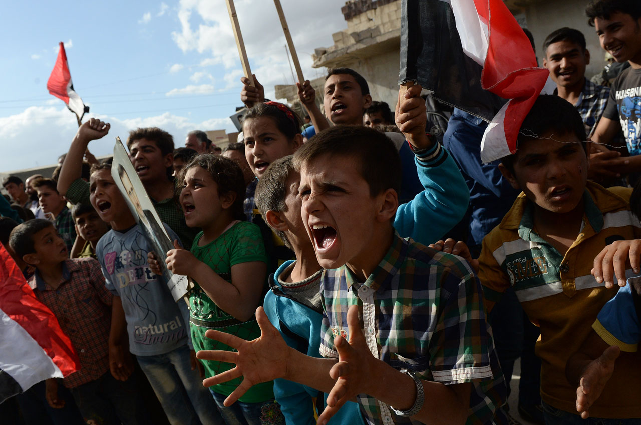 Syrian's react to the arrival of a Russian military convoy in a  small village near the city of Hama on May 4, 2016. Under pressure from Russia and the United States, the Syrian army agreed on to respect a two-day truce in the war-ravaged city of Aleppo. / AFP PHOTO / Vasily MAXIMOV / MOY