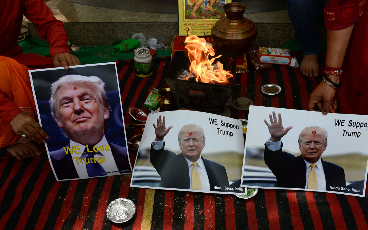In this photograph taken on May 11, 2016, an Indian Hindu priest performs a Hawan (The Sarced Fire) ritual alongside posters bearing the image of US Republican presidential candidate Donald Trump in New Delhi. Donald Trump may face a long, tough road to the White House, but some fans in India at least are pulling together to try and get him divine assistance. A far-right Hindu group held prayers in the Indian capital to support the presumptive Republican presidential nominee whom they hailed a fighter and a saviour of humanity.  / AFP PHOTO / Sajjad Hussain