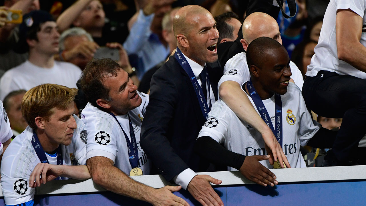 Real Madrid's French coach Zinedine Zidane (3rd L) celebrates after Real Madrid won the UEFA Champions League final football match between Real Madrid and Atletico Madrid at San Siro Stadium in Milan, on May 28, 2016.  PIERRE-PHILIPPE MARCOU / AFP