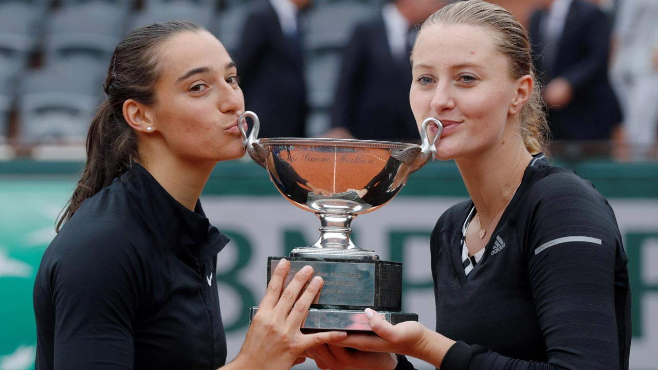 France's Caroline Garcia (R) and France's Kristina Mladenovic kiss the trophy after winning the women's double final match against Russia's Ekaterina Makarova and Russia's Elena Vesnina at the Roland Garros 2016 French Tennis Open in Paris on June 5, 2016. Thomas SAMSON / AFP