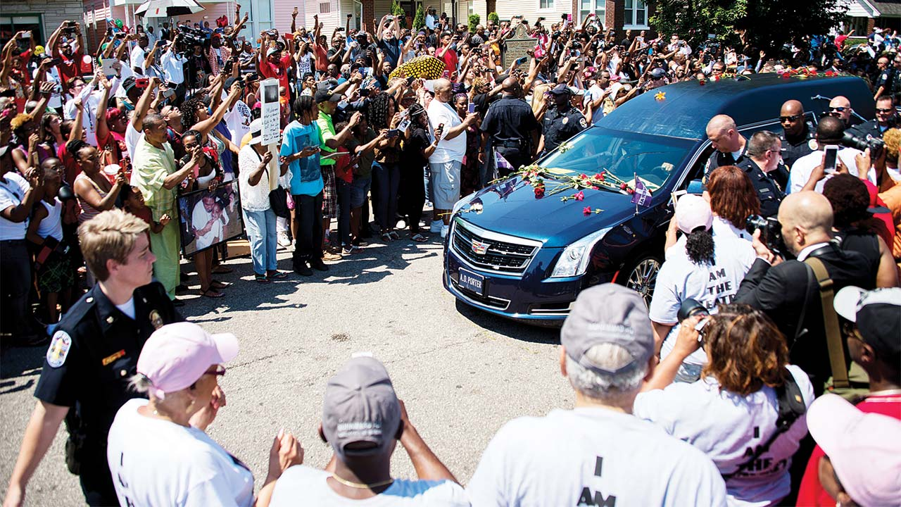The hearse carrying boxing legend Muhammad Ali stops outside his childhood home where mourners wait to pay their respects in Louisville, Kentucky... yesterday. PHOTO: JIM WATSON / AFP
