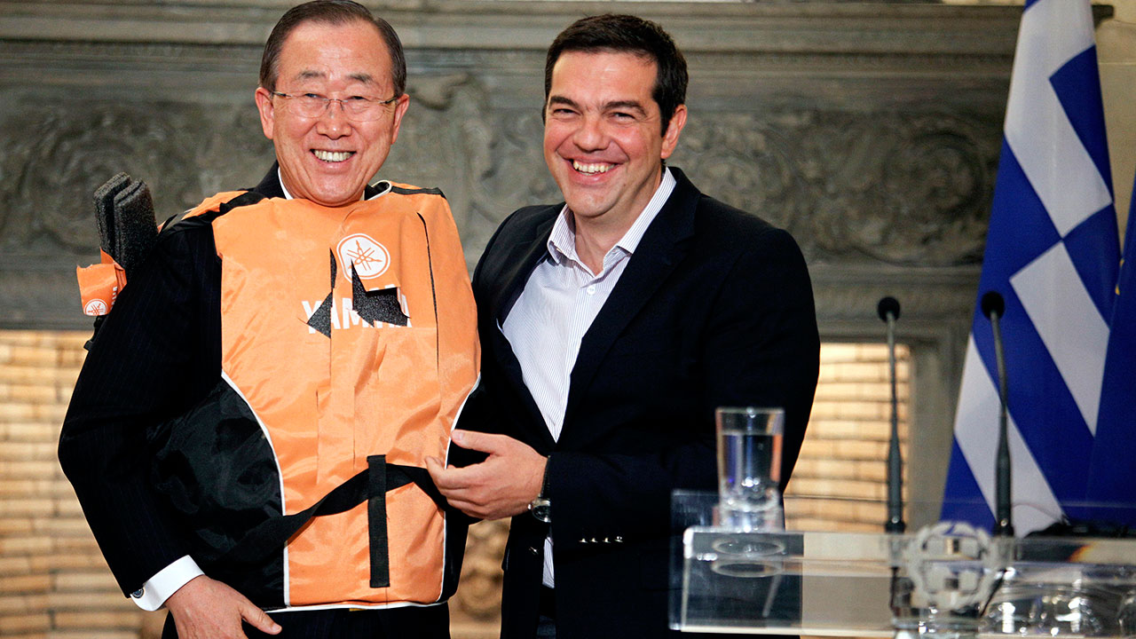 United Nations Secretary-General Ban Ki-moon (L) wears a life jacket he received from Greek Prime Minister Alexis Tsipras (R), after a press conference following their meeting in Athens on June 18, 2016. United Nations Secretary-General Ban Ki-moon concludes a two-day visit to Greece by meeting Greek Prime Minister Alexis Tsipras and flying to the island of Lesbos, a focal point in Europe's migration crisis and the main destination for thousands crossing the Aegean sea from Turkey. Yorgos KONTARINIS / Eurokinissi / AFP
