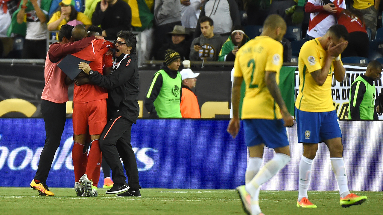 Members of Peru's national team (in red) celebrate after defeating Brazil in their Copa America Centenario football tournament match in Foxborough, Massachusetts, United States, on June 12, 2016. / AFP PHOTO / Timothy A. CLARY