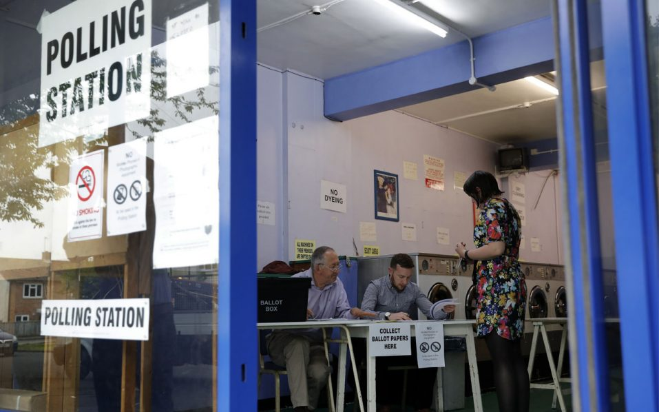 A presiding officer and poll clerk greet an early morning voter at a polling station set up in a launderette in Headington outside Oxford on June 23, 2016. Millions of Britons began voting today in a bitterly-fought, knife-edge referendum that could tear up the island nation's EU membership and spark the greatest emergency of the bloc's 60-year history. / AFP PHOTO / ADRIAN DENNIS