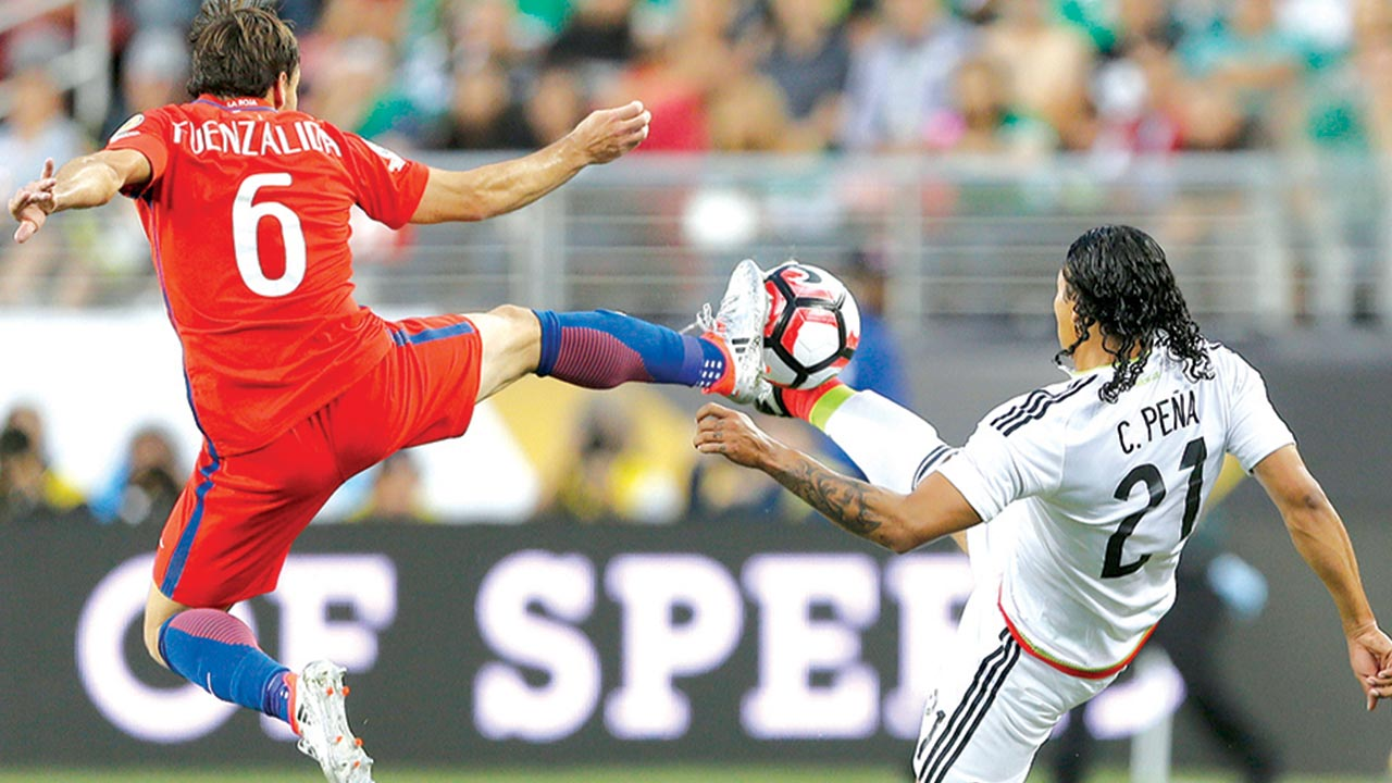 Mexico's Carlos Pena (right) vies for the ball with Chile's Jose Fuenzalida during a Copa America Centenario quarterfinal football match in Santa Clara, California, United States, on Saturday. Chile defeated Mexico 7-0 and qualified for semi-finals. PHOTO: AFP