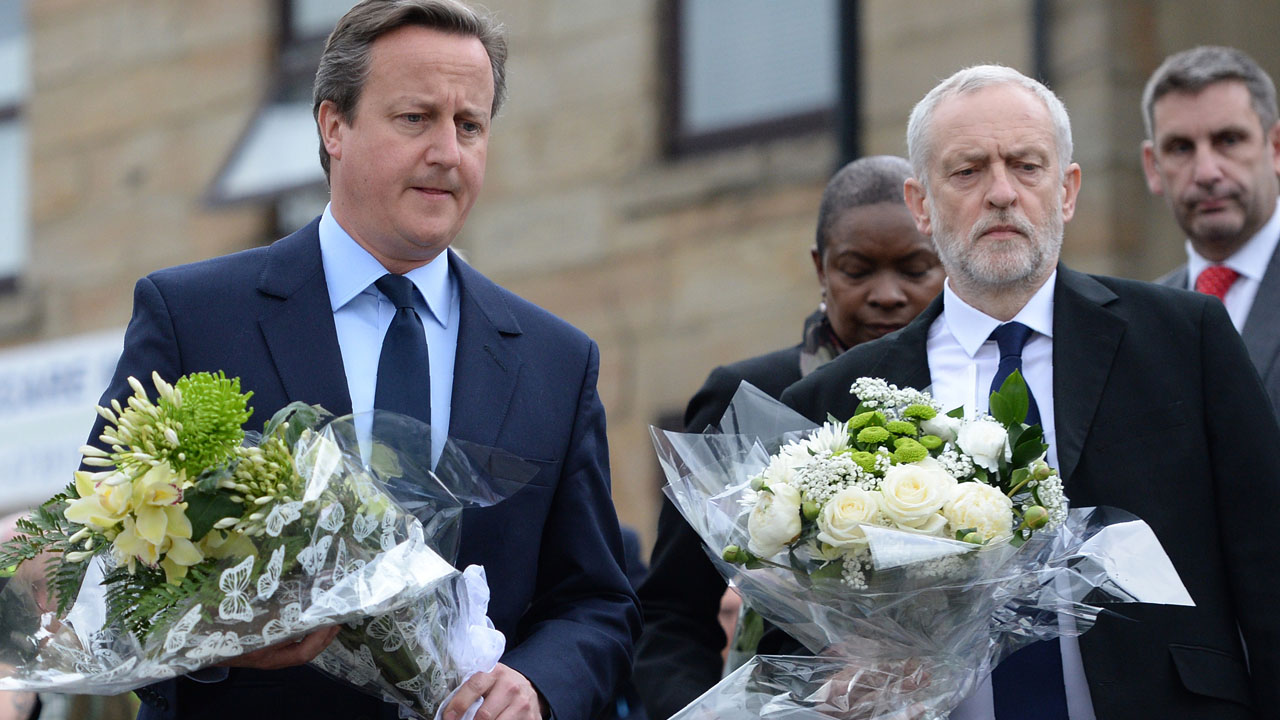 British Prime Minister David Cameron (L) and Labour Party leader Jeremy Corbyn (2R) prepare to lay flowers in memory of slain Labour MP Jo Cox, in Birstall, northern England, on June 17, 2016. Labour MP Jo Cox, a 41-year-old former aid worker also known for her advocacy for Syrian refugees, was killed on June 16, outside a library where she was supposed to meet constituents in Birstall in northern England, just a few miles (kilometres) from where she was born. / AFP PHOTO / OLI SCARFF