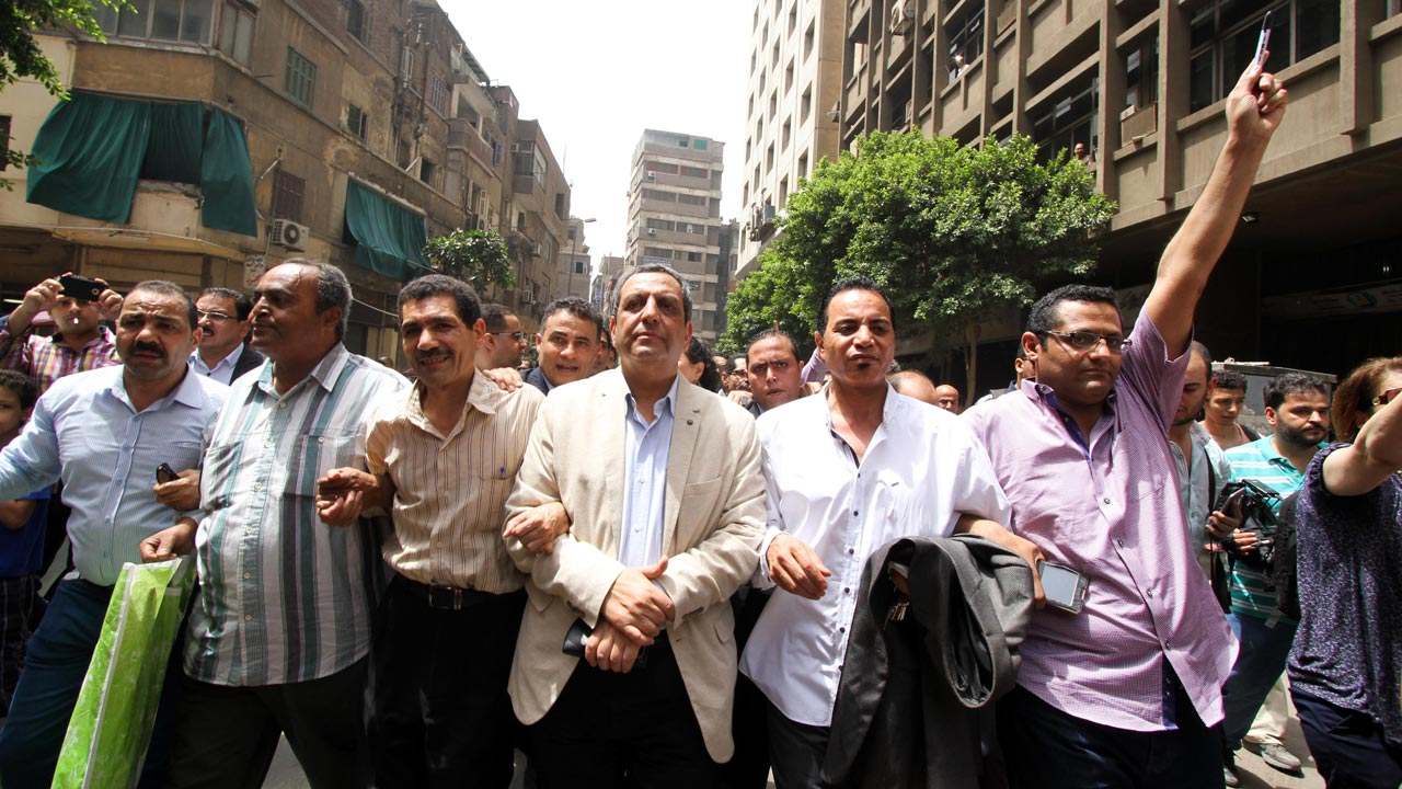 Egyptian Journalists Syndicate president Yahiya Kallash (C), secretary general Gamal Abd el-Rahim (2-R), and freedoms committee chief Khaled el-Balshy (R) march and shout slogans after leaving the courthouse in Cairo on June 4, 2016. The three top members of Egypt's journalists' union have been charged with aiding fugitives after two reporters sought by police staged a sit-in at the union's offices. The hearing on June 4 lasted a few minutes only and the trial was adjourned to June 18 at the request of defence lawyers who asked for more time to review the case, an AFP reporter and one of the lawyers said.  STR / AFP