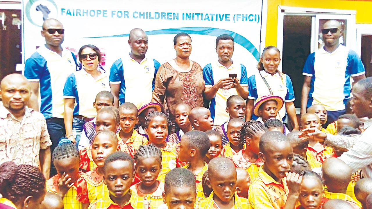 Officials of Fairhope for Children Initiative (FHI), with a cross section of pupils of One Master Model School, during festivities to mark this year's Children's Day in Lagos