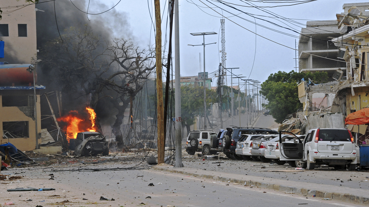 Fire is seen at the scene of a car bomb attack claimed by Al-Qaeda-affiliated Shabaab militants which killed at least 5 people, on the Naasa Hablood hotel in Mogadishu on June 25, 2016. The hotel in southern Mogadishu is often used by politicians and members of the Somali diaspora visiting the city. The attack came just three weeks after another assault quickly claimed by the Al-Qaeda-linked Shabaab group on the city's Ambassador hotel left 10 dead including two lawmakers when a huge car bomb ripped the front off the six-storey building. / AFP PHOTO / MOHAMED ABDIWAHAB