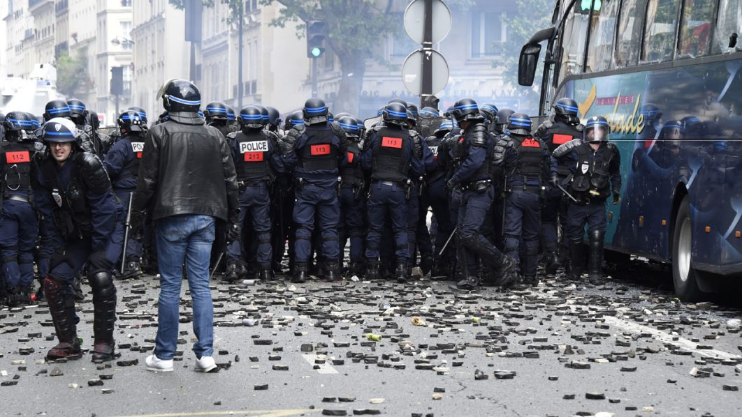 French anti-riot police officers stand as stones and rubbish lie on the pavement during a demonstration against proposed labour reforms in Paris on June 14, 2016.  Several hundred masked protesters hurled objects at police on June 14 during a demonstration in Paris against a contested reform of French labour laws, authorities said.  / AFP PHOTO / DOMINIQUE FAGET