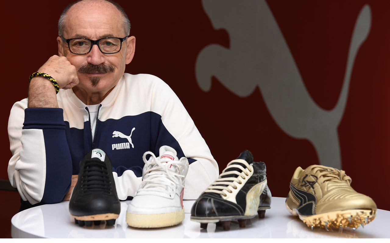 Helmut Fischer, former employee and archivist of the German sports goods company Puma, poses with shoes of former international athlete's, pictured at the headquarters of Puma in Herzogenaurach, southern Germany, on June 3, 2016.  / AFP PHOTO / CHRISTOF STACHE / TO GO WITH AFP STORY BY ROMAIN FONSEGRIVES