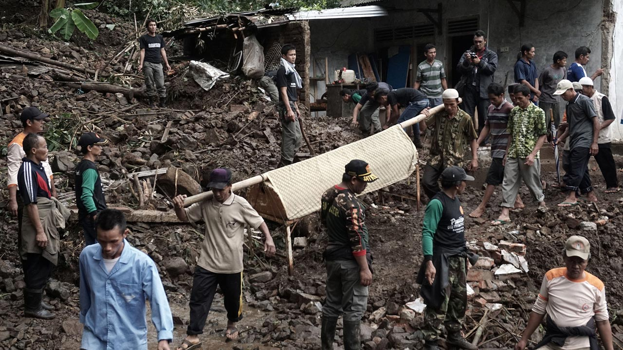 Indonesian villagers and search and rescue team members carry out the body of a landslide victim at Gumelem Kulon village in Banjarnegara on June 19, 2016. Flash flooding and landslides in Indonesia have killed 24 and left more than two dozen missing, an official said on June 19, with mud avalanches burying people inside their homes. ROHMAT SYARIF / AFP