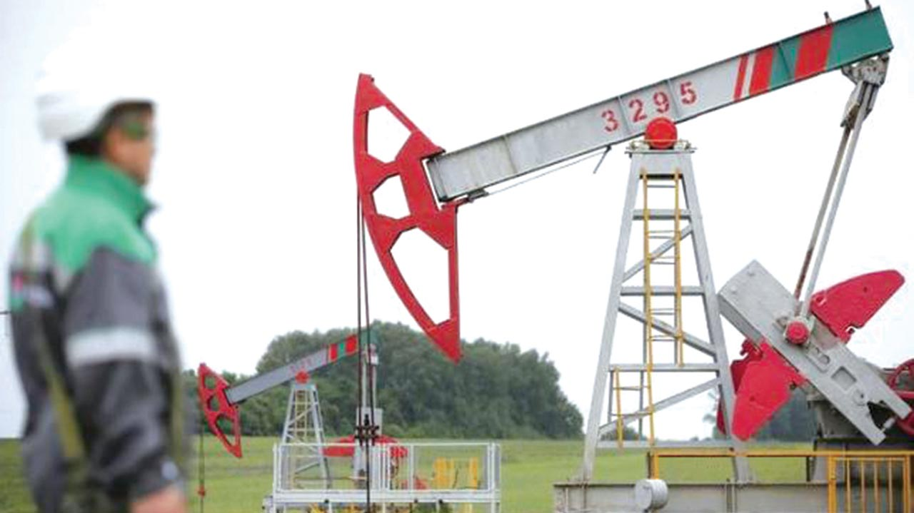 A worker looks at a pump jack at an oil field Buzovyazovskoye owned by Bashneft Company, North from Ufa, Bashkortostan, Russia.