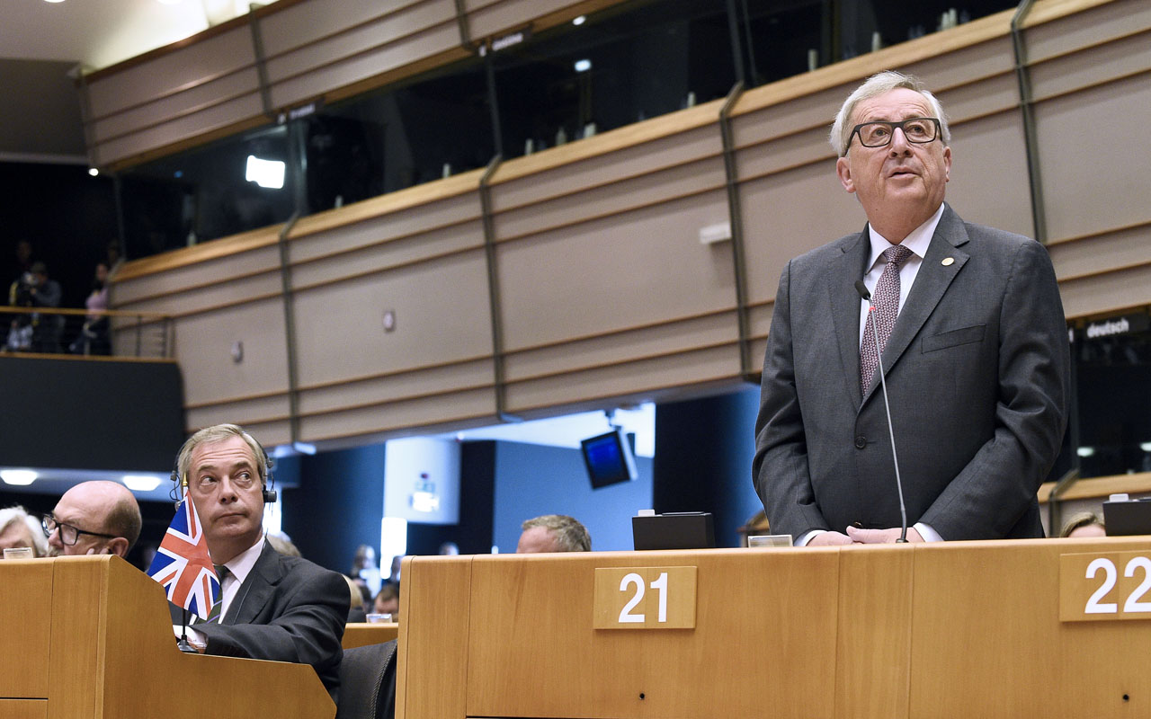 United Kingdom Independence Party (UKIP) leader Nigel Farage (L) looks at European Union Commission President Jean-Claude Juncker as he delivers a speech the European Union headquarters in Brussels on June 28, 2016 ahead of a plenary session. European Commission chief Jean-Claude Juncker called on June 28 on Prime Minister David Cameron to clarify quickly when Britain intends to leave the EU, saying there can be no negotiation on future ties before London formally applies to exit. European leaders gather in Brussels for a crunch two-day summit set to be dominated by Britain's departure from the bloc following its shock referendum last week. / AFP PHOTO / JOHN THYS