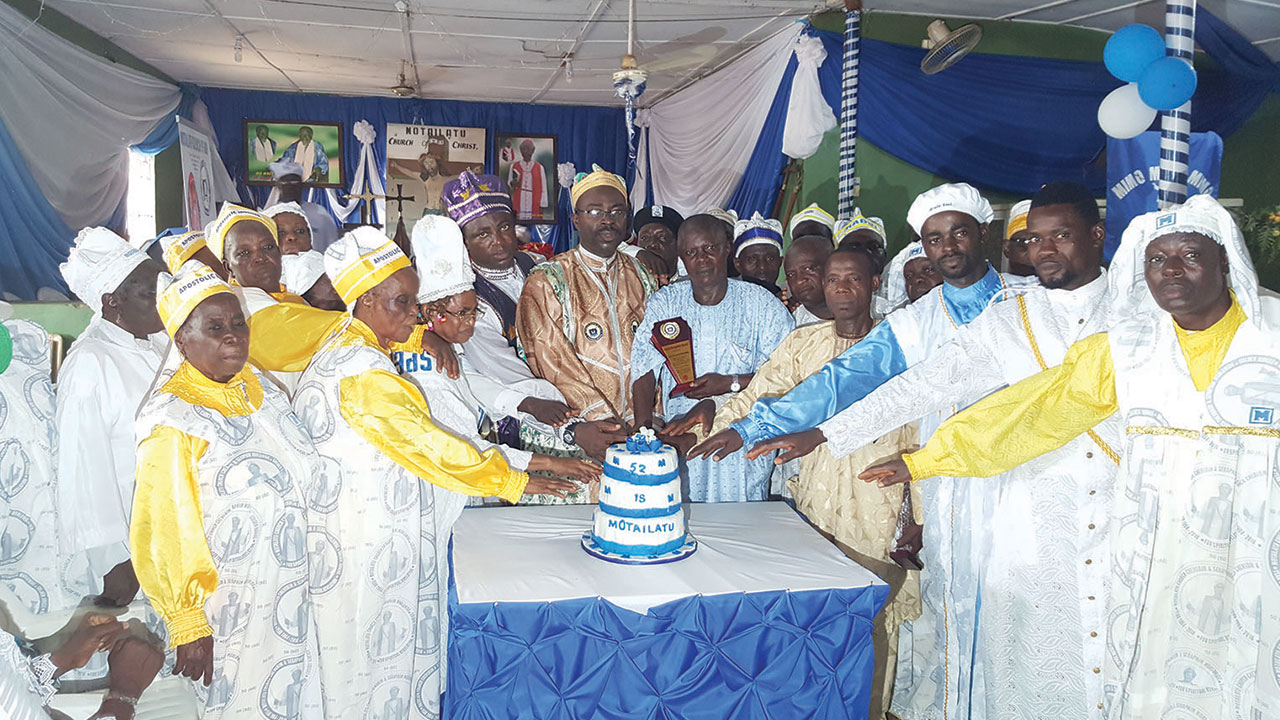Snr. Superintendent Akinadewo (middle) with some elders cutting the anniversary cake.