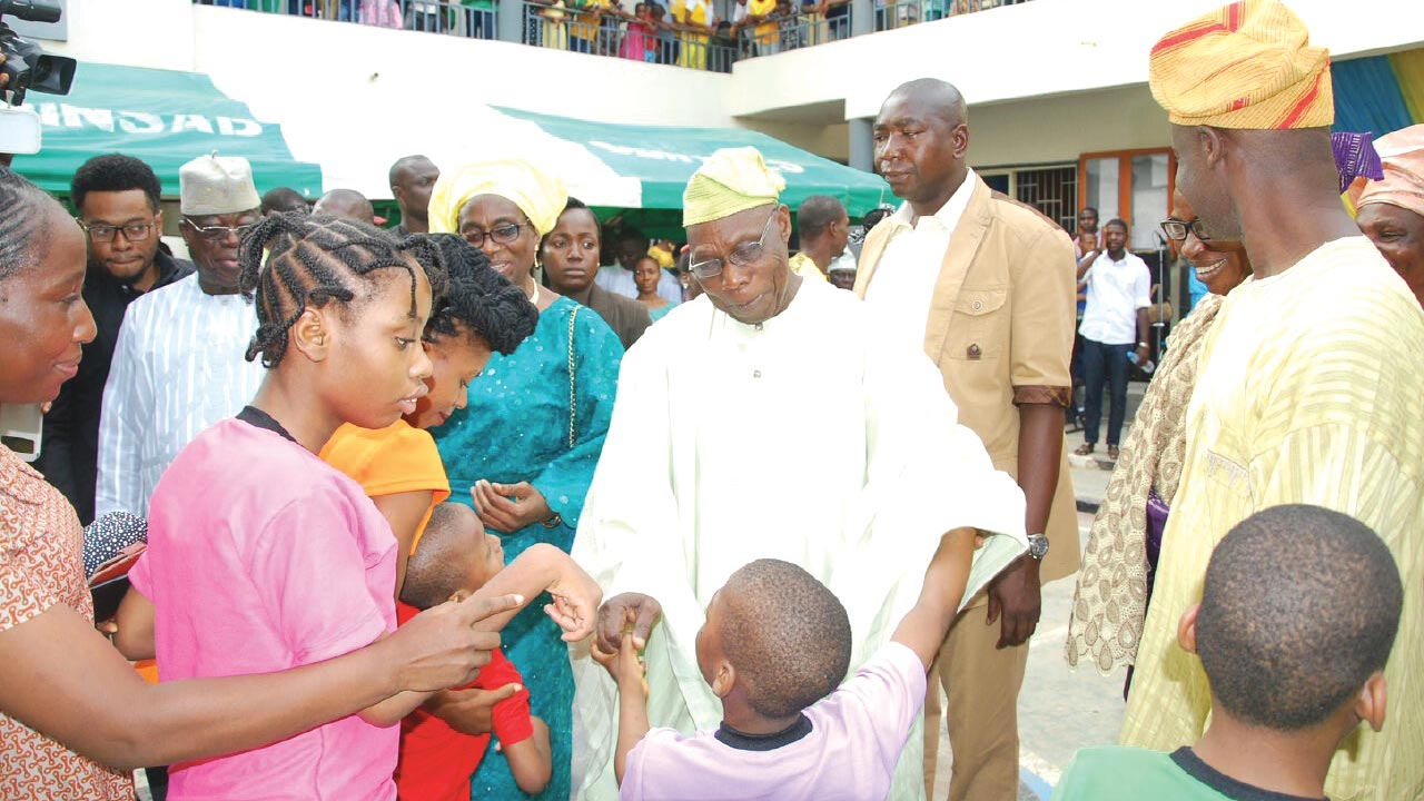 Former Presisdent Olusegun Obasanjo interacting with some of the physically challenged children at the commissioning of Do-Est Dot International School, Lagos
