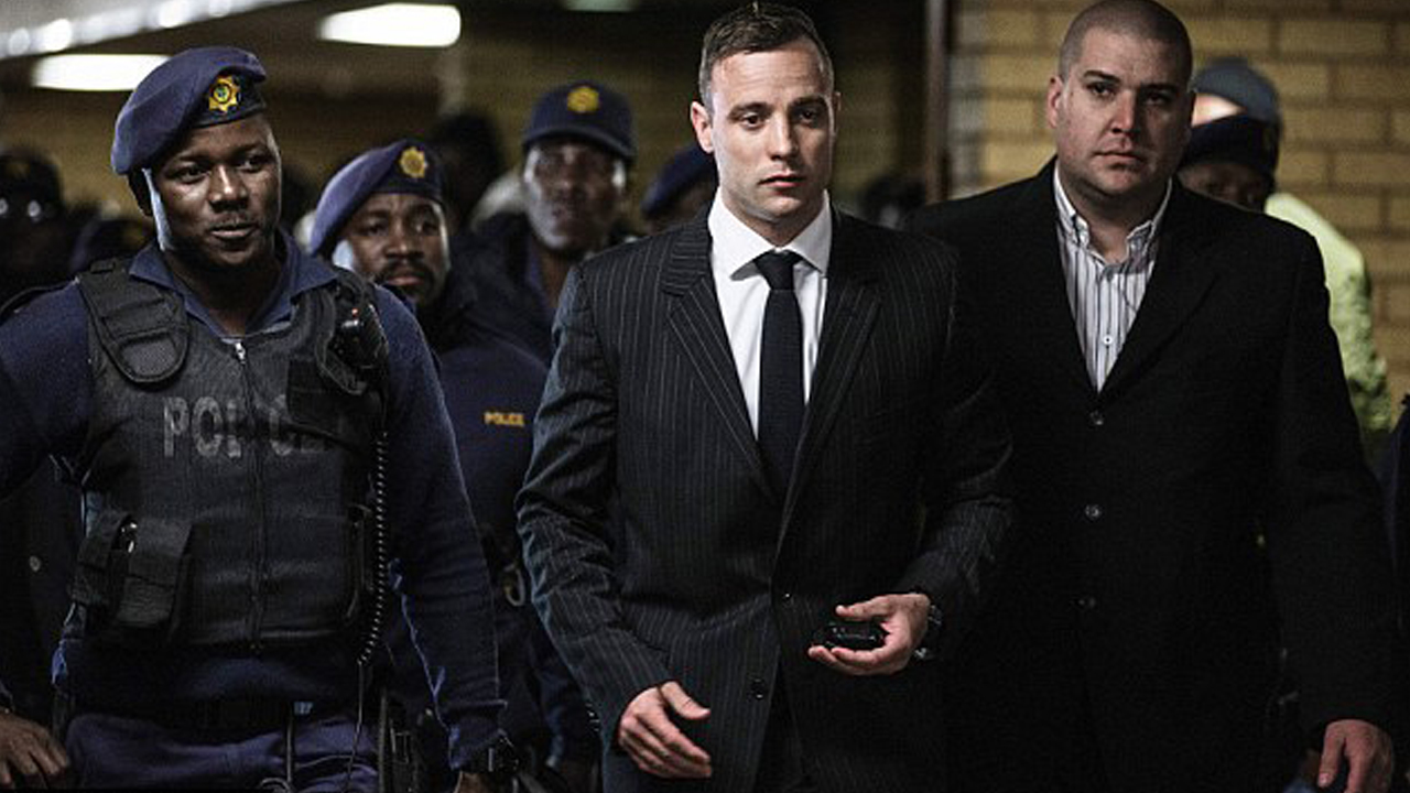 Oscar Pistorius was flanked by police officers as he made his way to Pretoria High Court for the sentencing hearing. PHOTO: AFP