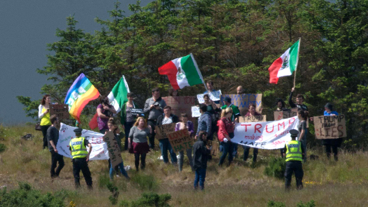 "A group of protesters wave Mexican flags on the hillside above the Trump International Golf Links minutes before presumptive Republican presidential nominee, Donald Trump's arrival at the course, north of Aberdeen on the East coast of Scotland, on June 25, 2016. Donald Trump hailed Britain's vote to leave the EU as ""fantastic"" shortly after arriving in Scotland on Friday for his first international trip since becoming the presumptive Republican presidential nominee. / AFP PHOTO / Michal Wachucik"