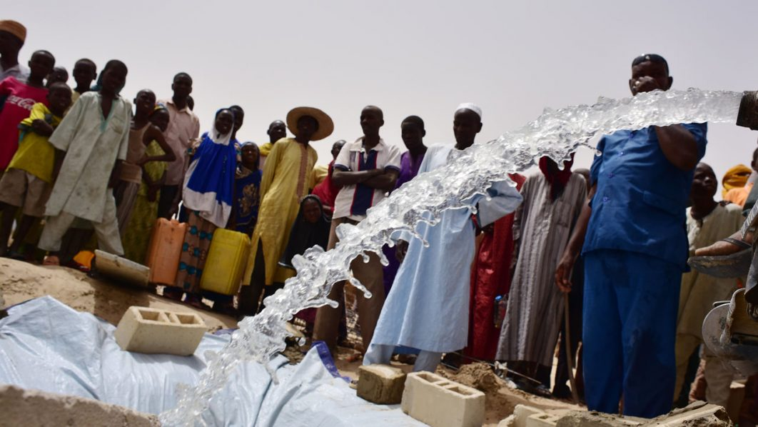 Displaced people look at the under construction water reservoir built by the UN system in a refugees camp of Kidjendi, around Diffa, southeastern Niger, on June 19, 2016.  / AFP PHOTO / ISSOUF SANOGO