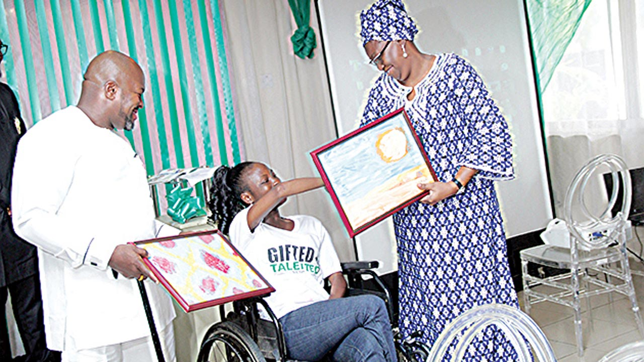 Akiin Shuga (left) and Mrs Fashola present gifts to a receipeient.