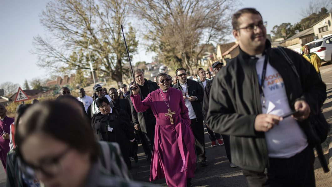South Africa's Bishop Malusi Mpumlwana (C) leads a peace walk in Soweto on June 11, 2016 to commemorate the 40th anniversary of the Soweto Uprising - when police opened fire at black students protesting against the use of Afrikaans as the primary language in their schools - marking one of the defining moments of the anti-apartheid struggle.  Four days ahead of the 40th anniversary of the June 16, 1976 students Uprising the South African Council of Church has organized this event aiming to reconcile and heal the wounds of the past. AFP PHOTO/GIANLUIGI GUERCIA / AFP PHOTO / GIANLUIGI GUERCIA