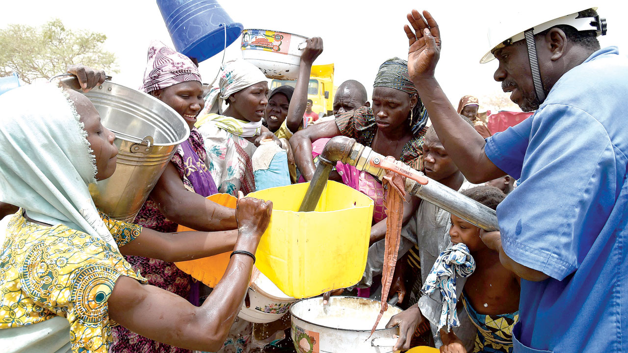 Displaced people gather to collect water in a camp for displaced populations near Diffa. PHOTO: ISSOUF SANOGO / AFP