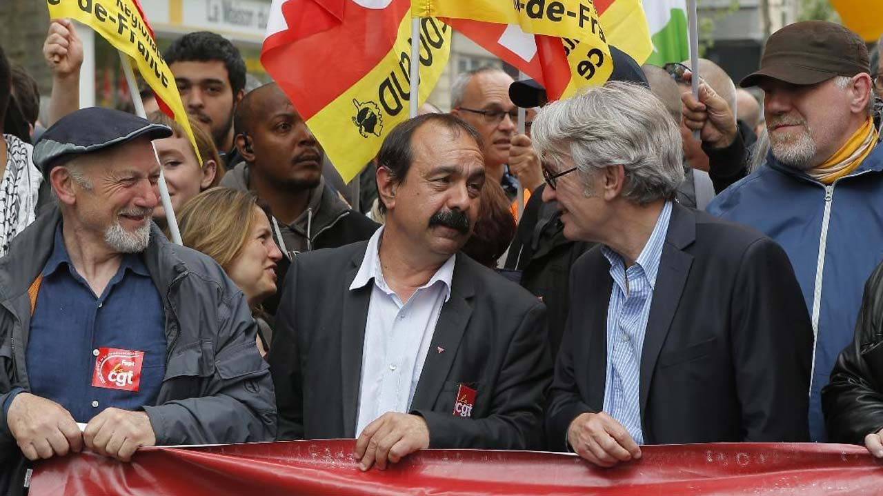 CGT trade union leader Philippe Martinez, center left, speaks with French union FO, Force Ouvriere, secretary general Jean-Claude Mailly, right, during a demonstration held as part of nationwide labor actions in Paris, France, Thursday, May 26, 2016. French protesters scuffled with police, dock workers set off smoke bombs and union activists disrupted fuel supplies and nuclear plants Thursday in the biggest challenge yet to President Francois Hollande's government as it tries to give employers more flexibility. (AP Photo/Francois Mori)