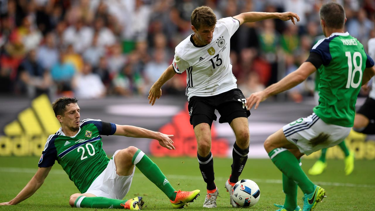 Germany's midfielder Thomas Mueller (C) and Northern Ireland's defender Craig Cathcart and Northern Ireland's defender Aaron Hughes vie for the ball during the Euro 2016 group C football match between Northern Ireland and Germany at the Parc des Princes stadium in Paris on June 21, 2016. LIONEL BONAVENTURE / AFP