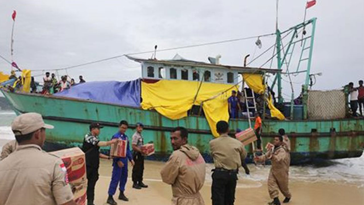Indonesian officials load food supplies onto a boat carrying Tamil migrants which had been stranded on the beach for the last few days in Lhoknga, Aceh province in Indonesia. (AP Photo)