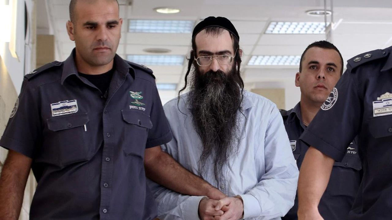 Ultra-Orthodox Jew Yishai Shlissel (C), who was convicted of killing a 16-year-old Israeli girl during the Jerusalem Gay Pride parade last year, is escorted into court by police on June 26, 2016 in Jerusalem (AFP Photo/Gali Tibbon)